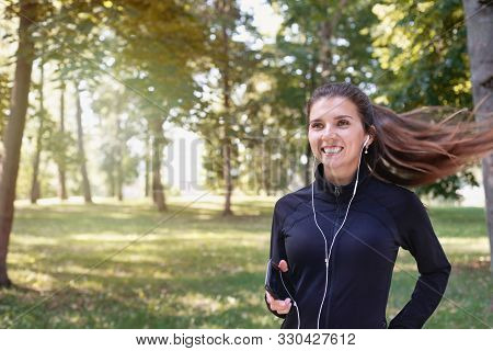 Portrait Of Young Smilling Sporty Brunette Woman Running With Headphones In The Park Outdoor