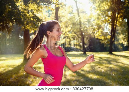 Portrait Of Young Smilling Sporty Brunette Woman Running In The Park Outdoor