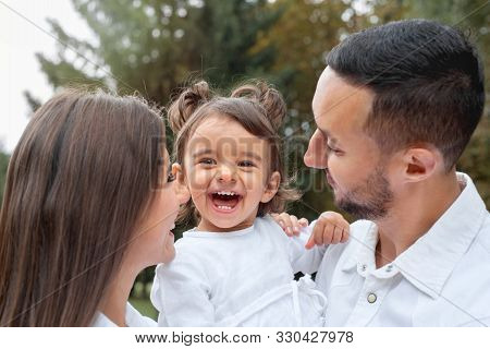 Happy Little Girl Laught With Her Parents In The Park