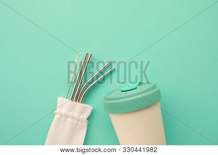Reusable Eco Friendly Bamboo Cup And Stainless Steel Metal Straws On Mint Background.