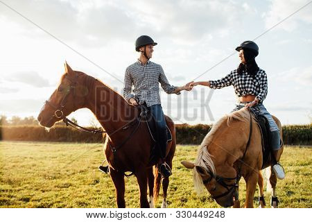 Happy Loving Couple Spending Time With Horses On Ranch