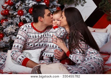Family In Pajamas Sits On A Bed Near The Christmas Tree Mom, Dad And Toddler, Idyll, Christmas Celeb