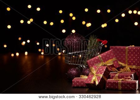 Shopping trolley, gift boxes and Christmas decoration with LED lights garland on a black background, Christmas and New Year shopping. Winter sale.