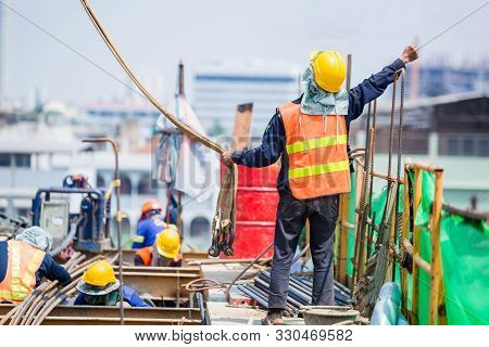 Construction Team Working At Height Site. Construction Workers Raising Hands To Signal Construction