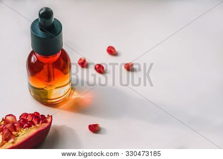 Pomegranate Seed Oil, Serum With Piece Of Pomegranate On White Background. Lifestyle, Copy Space