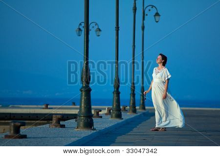 Happy beautiful woman on maxi white dress on a pier on a summer day poster