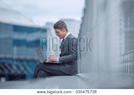 smiling corporate man with a take-away coffee, sitting next to an office building