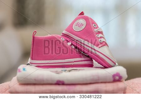 Pile Of Baby Clothes And Pink Girl Shoes. Pregnant Woman Is Getting Ready For The Maternity Hospital
