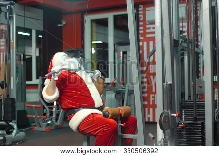 Santa Claus Training At The Gym On Christmas Day. Exercise-machine.