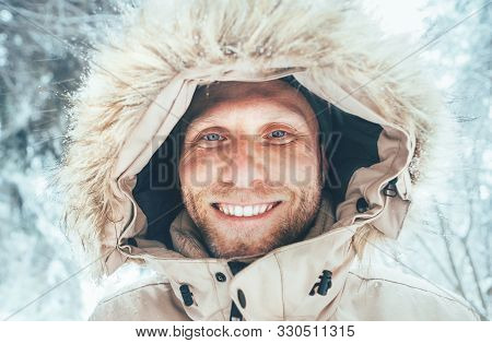Man Dressed In Warm Hooded Casual Parka Jacket Outerwear Walking In Snowy Forest Cheerful Smiling Fa