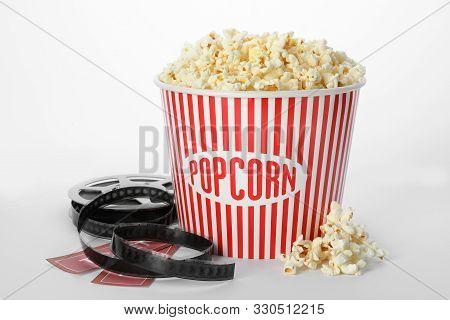 Bucket Of Fresh Popcorn, Tickets And Movie Reel On White Background. Cinema Snack
