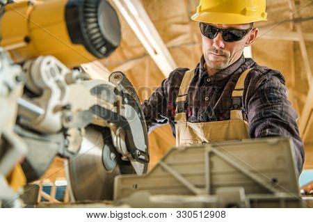 Caucasian Construction Contractor In His 30s Working With Power Tool. Powerful Circular Wood Saw. In