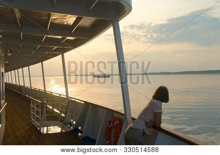 Women And The Sunset On The River. Woman From The Deck Of A Cruise Boat Watching At The Sunset And A