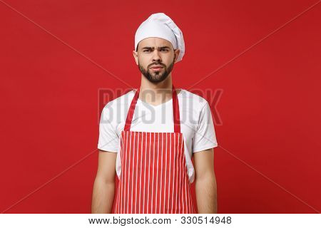 Puzzled perplexed young bearded male chef cook or baker man in striped apron white t-shirt toque chefs hat posing isolated on red background, studio portrait. Cooking food concept. Mock up copy space. poster