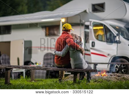 Rv Campsite Family Time. Father Hugging His Daughter On Wooden Bench In Front Of Campfire And Motorh