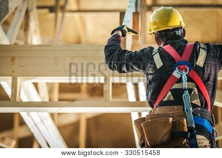 Wood Construction Worker. Caucasian Builder Wearing Safety Harness And The Wooden House Structure. I