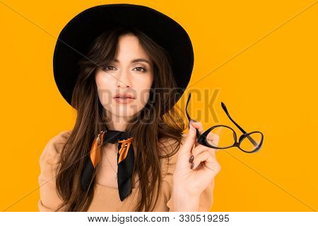 Stylish European Girl On An Orange Background With Glasses For Sight In Hands