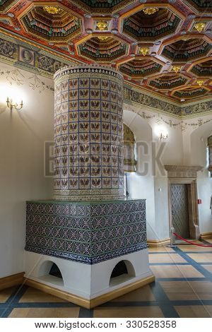 Mir, Belarus -  23-october-2019: Ornate Retro Tiled Stove And Decorated Carved Ceiling In Vintage Di