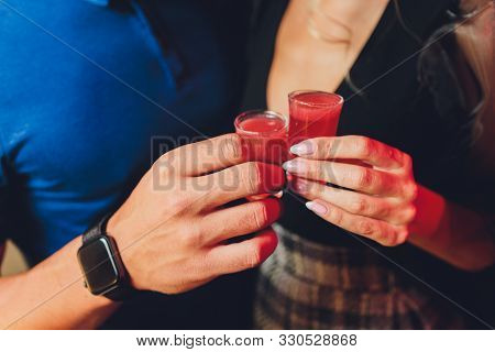 Clinking Glasses With Alcohol And Toasting, Party. Red Alco Shots