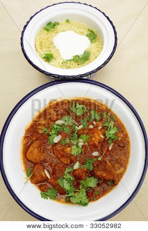 A meal of chicken tagine stew in a spicy, nutty tomato sauce, served with couscous and yoghurt