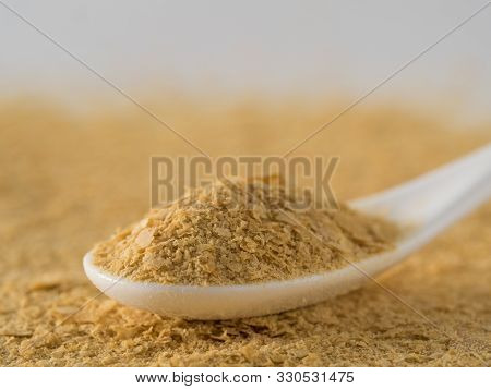 Nutritional Yeast Background. Nutritional Inactive Yeast In White Spoon. Copy Space. Nutritional Yea
