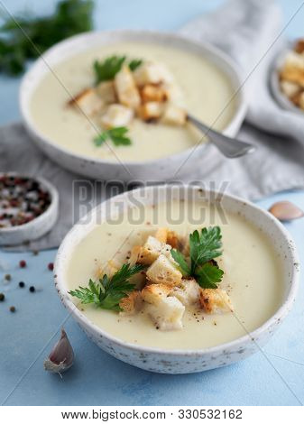 Cauliflower Potato Soup Puree On Blue Tabletop, Creamy Cauliflower Soup With Toasted Bread Croutons.