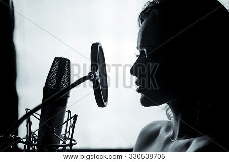 Young Woman With The Microphone In The Recording Studio. Professional Vocal Recording. Black And Whi