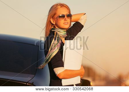 Young fashion blonde business woman with financial papers outside her car  Stylish female model in dark blue blazer and sunglasses