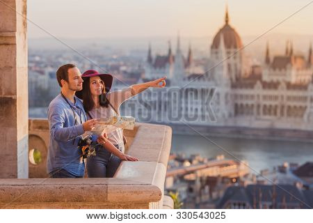 Young Couple Searching Right Direction On Map From The Point From Fisherman Bastion In Budapest With