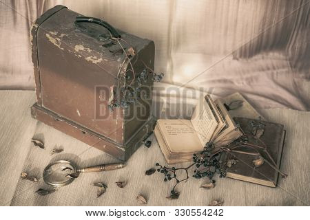 Old wooden chest, open books, dried grape brushes, magnifier. Vintage style. Concept of nostalgia, sadness, autumn loneliness, history poster