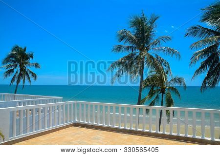 A Vibrant Tropical Blue And White Coloured Coastal Seascape With Palm Trees In A Blue Sky Viewed Fro