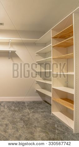 Vertical Frame Empty Walk In Closet Of A New House With Shelves Cabinets And Clothes Hangers