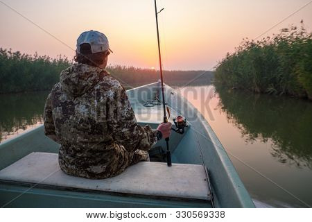 Young angler sits in the moving boat with fishing rod and enjoys sunset over the wall of reed