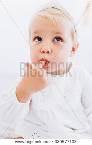 The Child Licks A Finger With An Appetite. Baby Girl In A White Dress.