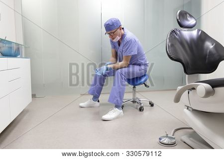 Wrist pain in the dental practice.Middle age dentist having short break for regeneration after long working hours, sitting on mobile dental saddle  in his office poster