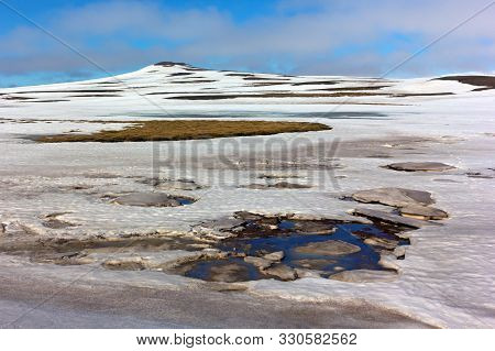 Mossy Fields Under Snow In Northern Iceland During Springtime. Panorama With Snow, Water And Mountai