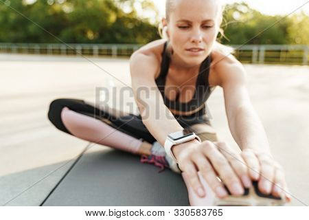 Image of focused young woman wearing tracksuit and earpods doing workout outdoors