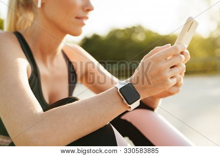 Image of young sportswoman wearing tracksuit and earpods holding cellphone while doing workout outdoors