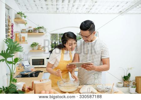 Young Asian Man And Woman Together Cooking Cake And Bread With Egg, Looking Menu From Tablet In The
