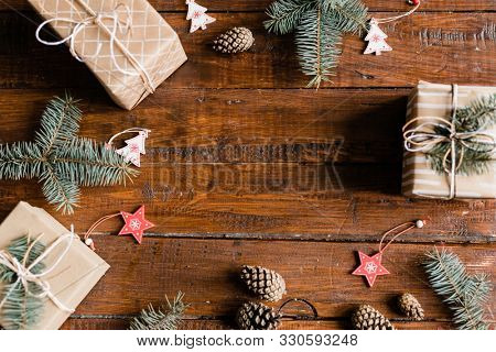 Christmas background made up of wrapped giftboxes, pinecones, conifer, decorative red stars and white firtrees