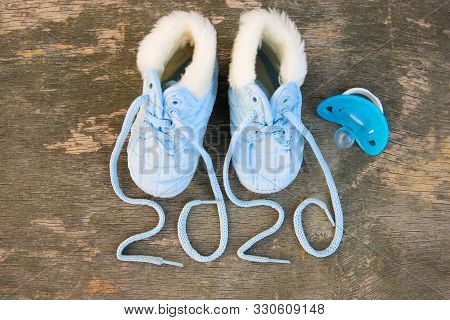 2020 New Year Written Laces Of Children's Shoes And Pacifier On Old Wooden Background. Top View. Fla