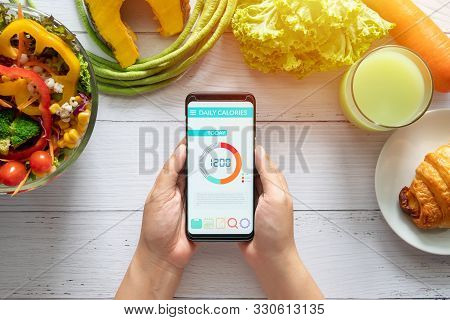 Calories Counting And Food Control Concept. Woman Using Calorie Counter Application On Her Smartphon