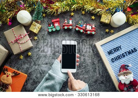 Online Shopping For Christmas Season And Gift Festival. Hand Holding Mobile Phone With Blank Screen