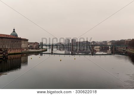 a view of the Garonne River as it passes through Toulouse, France, in a foggy day with the bridge Pont Saint Pierre in the background and the Hotel-Dieu Saint-Jacques on the left