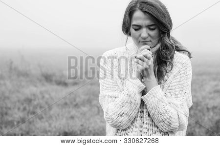 Girl Closed Her Eyes, Praying In A Field During Beautiful Fog. Hands Folded In Prayer Concept For Fa