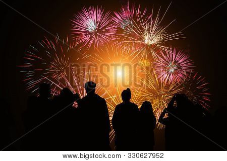 Crowd Watching Fireworks And Celebration. Happy Family Sitting On Floor And Watching The Fireworks C