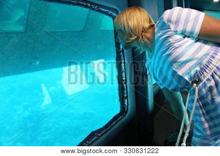 Modern Woman Looking Out Window At Bottom Of Excursion Ship. Girl Watching Sea Fishes Underwater Thr