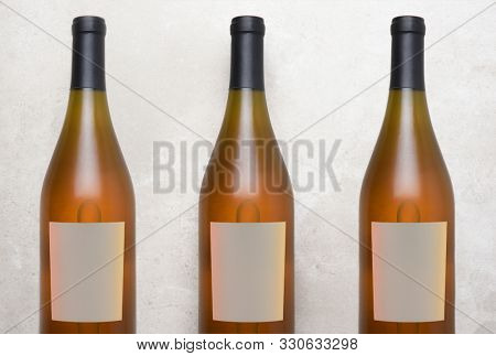 Chardonnay Wine: Top view of a three bottles with blank labels on a concrete counter top.