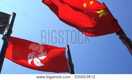 Hong Kong And Mainland China Red Flags In Blue Sky. Internal Political Affair Conflict