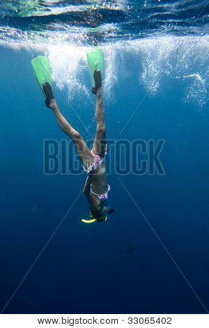 Young woman diving on a breath hold and fining in blue transparent sea